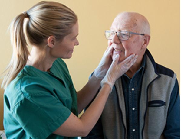 Senior som får hjelp av tannpleier
